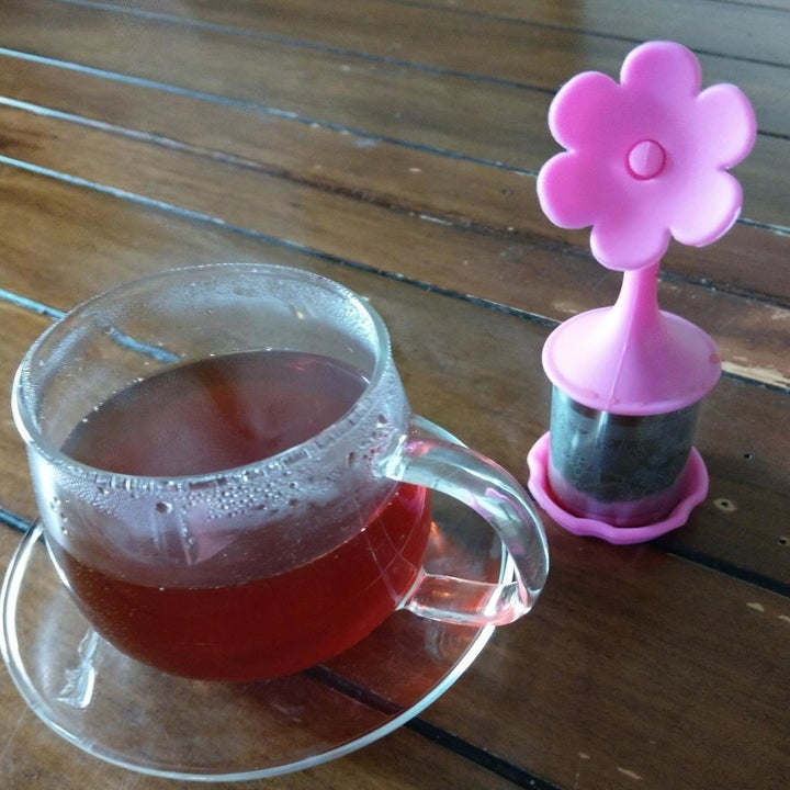 Pink floral tea infuser next to clear cup of brown tea on a table