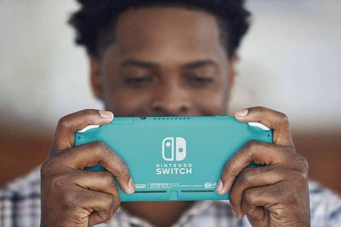 A man happily playing his Nintendo Switch Lite