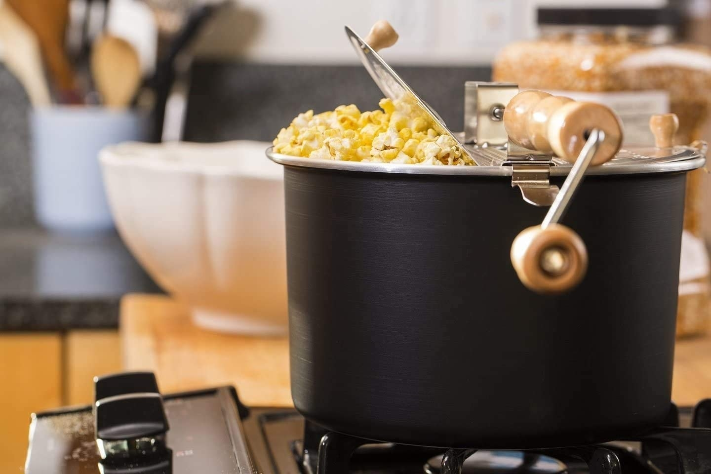 The popper, which is a black pot with a silver lid and wooden hand crank, on a stove