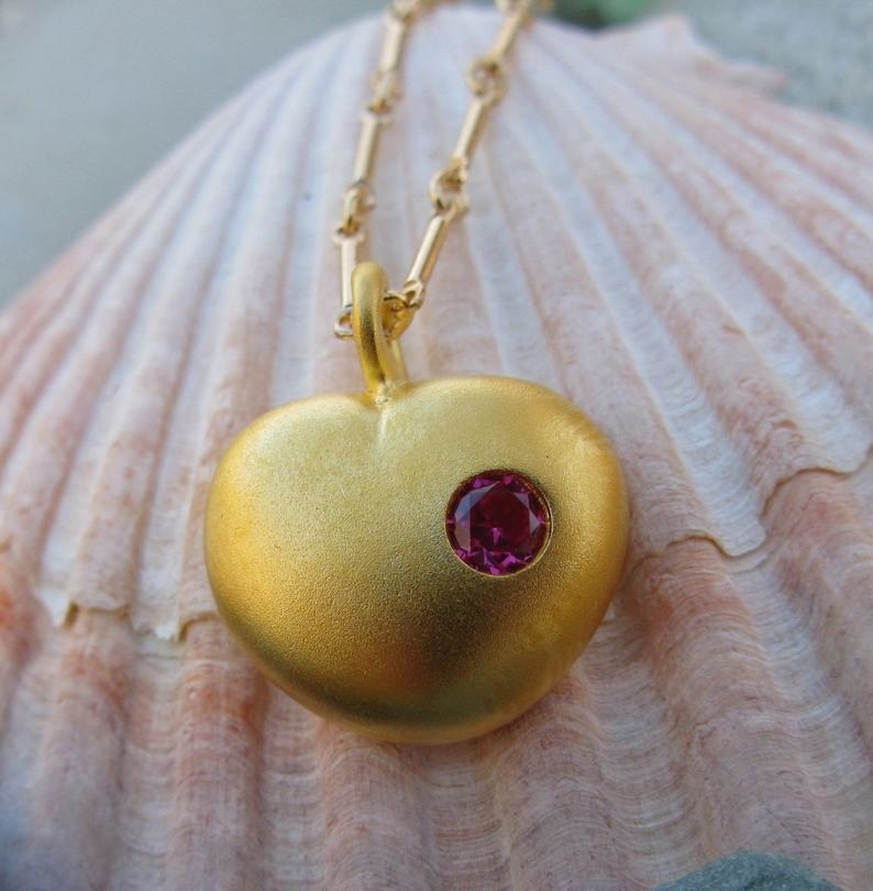 The gold heart shaped pendant with a pinkish-red stone