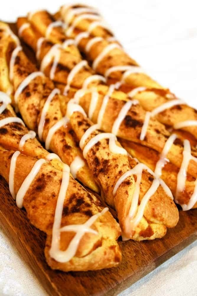 A wooden serving board topped with pumpkin twists drizzled with frosting.