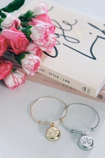 A silver and gold invisaWear bangle with a round charm sitting next to a stack of books and a bouquet of flowers