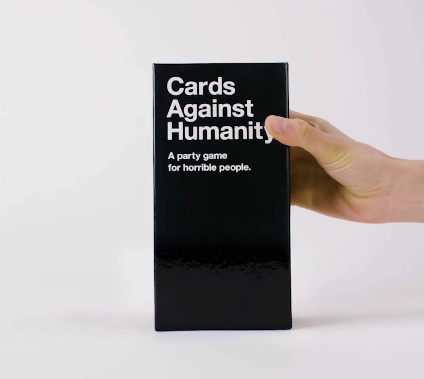Person is holding the box of Cards Against Humanity
