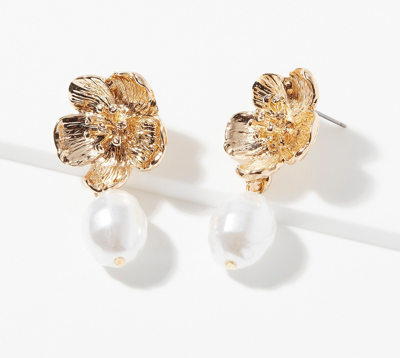 A pair of flower-shaped earrings on a plain background