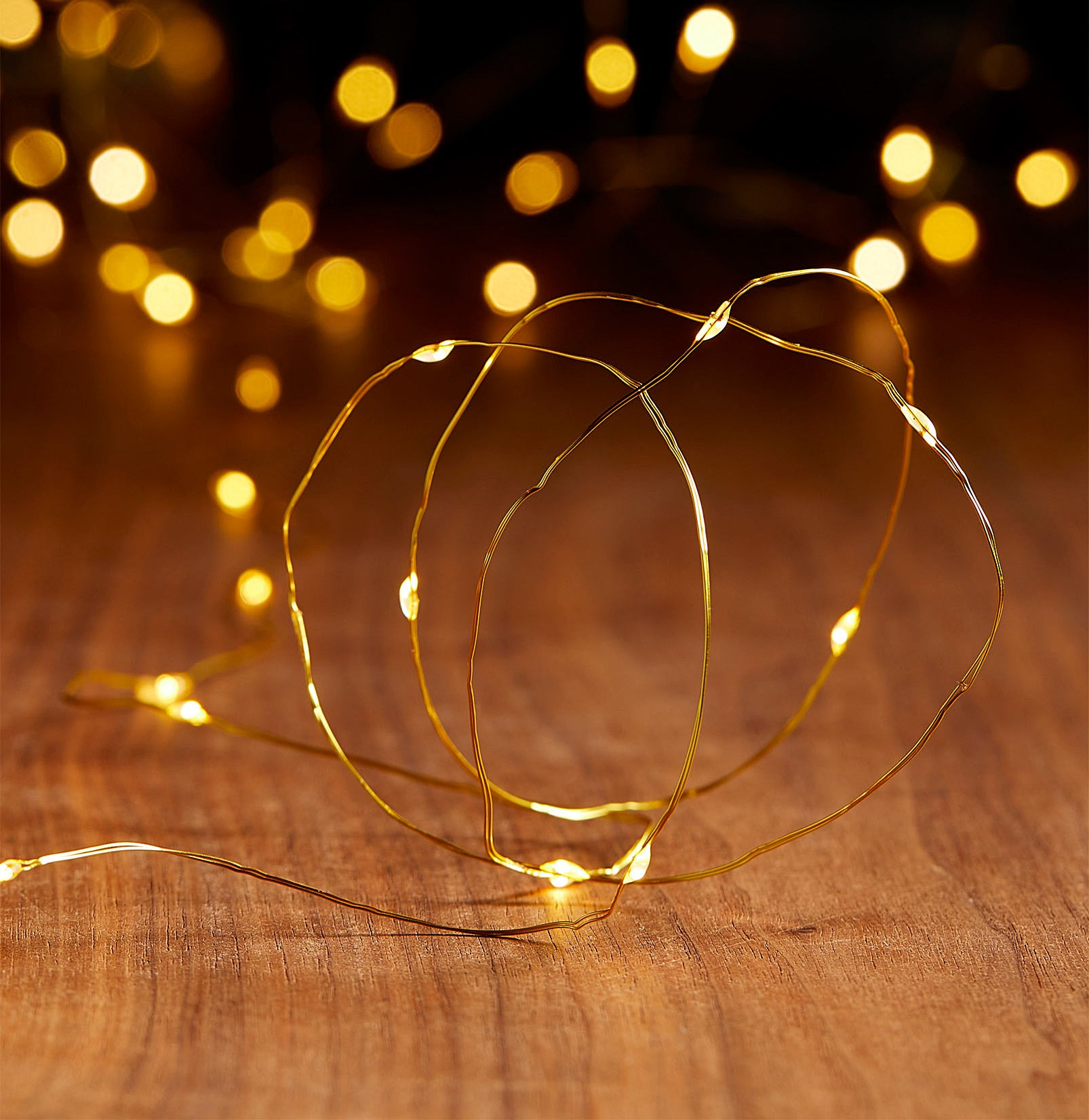 A long cord of fairy string lights on a wooden floor