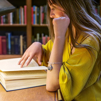 A model wearing an invisaWear bracelet sitting at a desk in a library reading a book