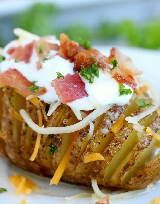A hasselback potato topped with sour cream, bacon, herbs, and cheese.