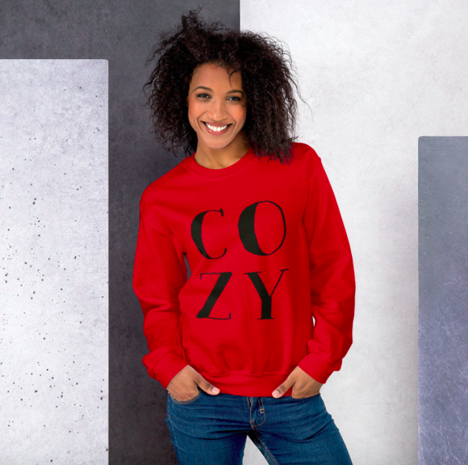 A smiling person wearing an oversized sweatshirt that says COZY