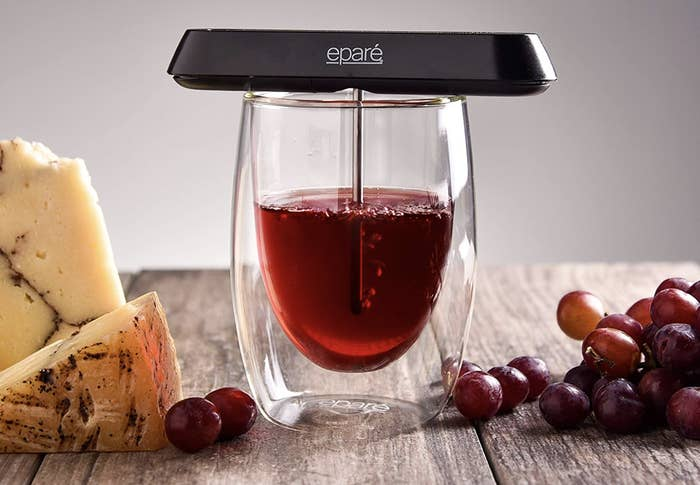 A small black device resting on a glass of wine with a metal tube in it, aerating the wine