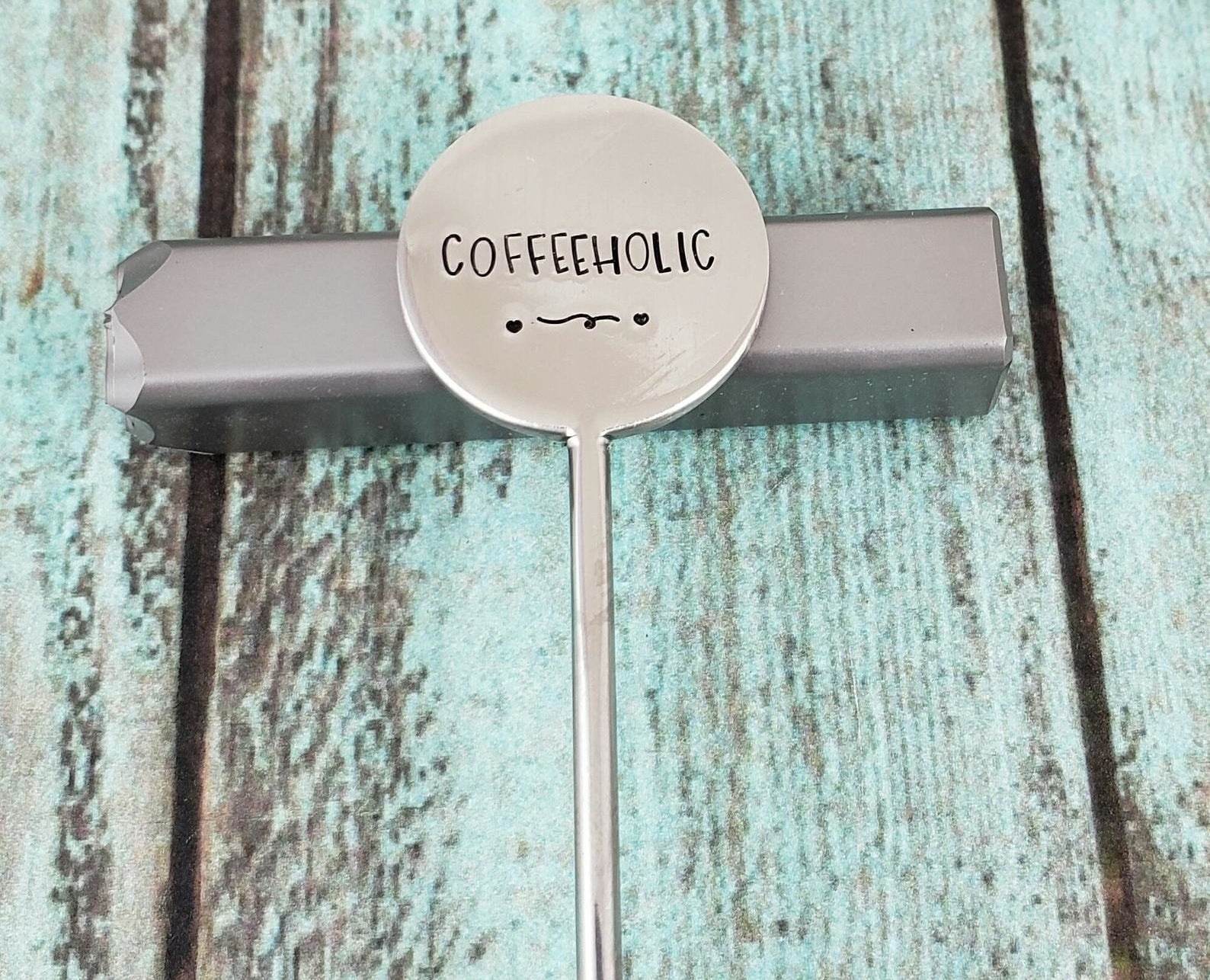 """the silver stirrer spoon with """"coffeeholic"""" engraved on it"""