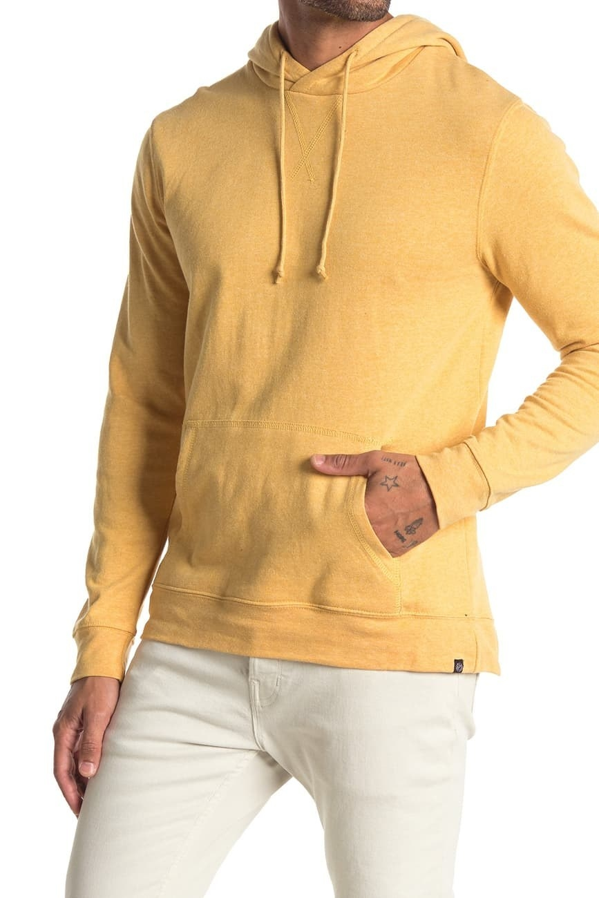 Model wearing the hooded sweatshirt with drawstring and a big front pocket in yellow