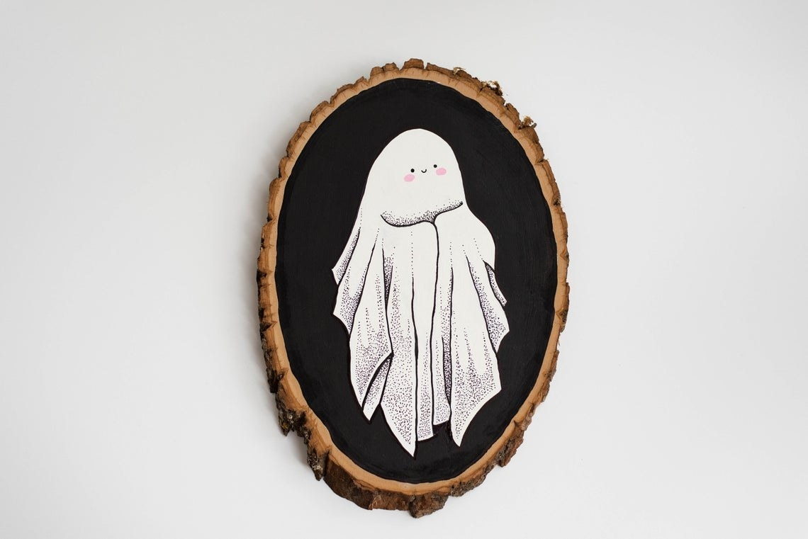 Oval wood piece with painted smiling ghost who has blushing cheeks