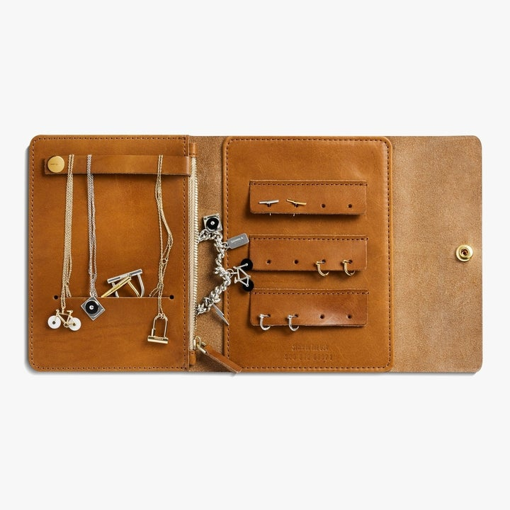 Shinola leather jewelry traveler in natural opened with various necklaces, rings, and bracelets store inside