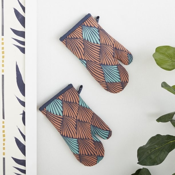 Two oven mitts hanging on the wall with an orange, teal, and navy petal-like pattern on them