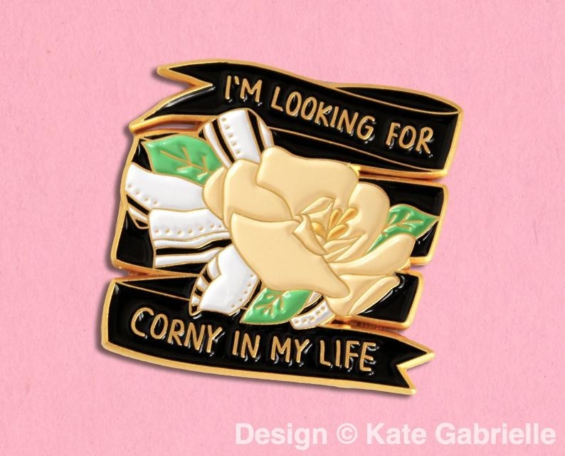 "The black, white, peach, green, and gold pin with a corsage and the words ""I'm looking for corny in my life"""