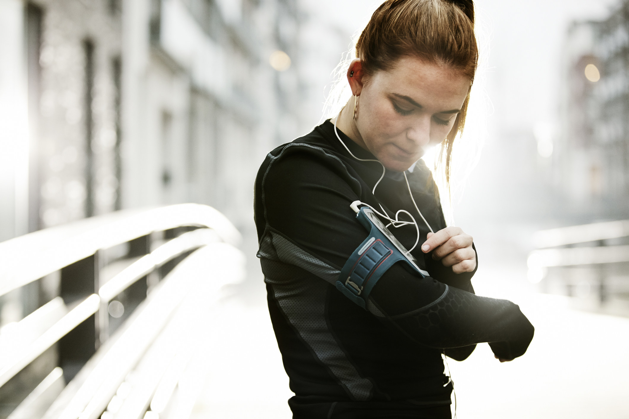 A model wearing an armband with their phone attached to it for a workout