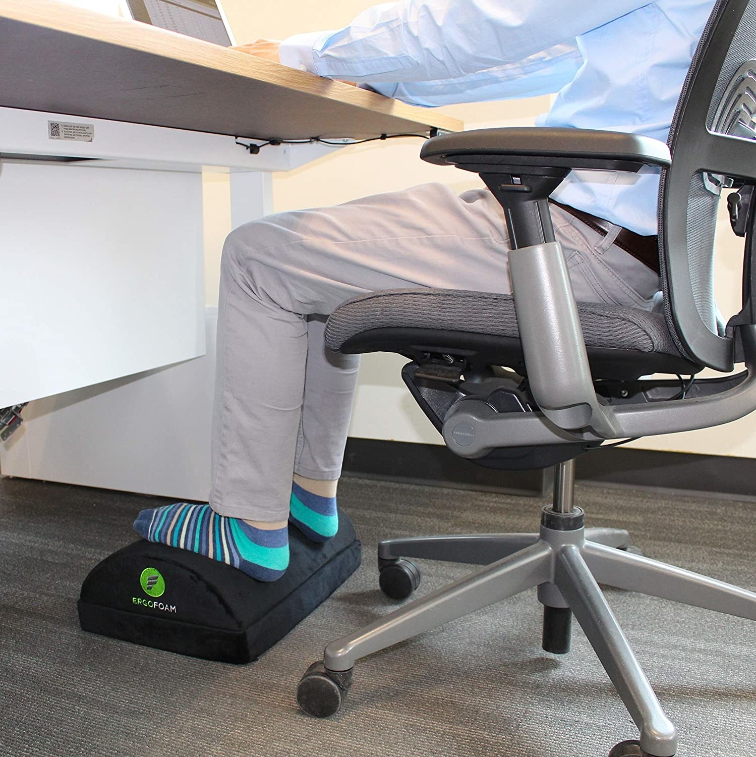 Model places feet on top of black rounded footrest while typing at a desk
