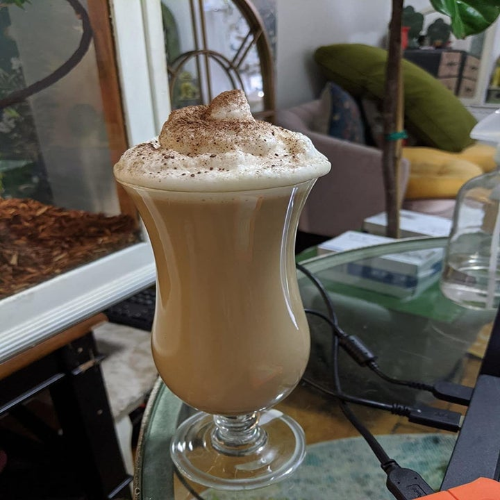 a tall glass filled with espresso and frothy milk