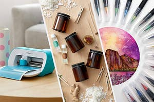 A Cricut joy cutting machine on a table, four glass candle jars surrounded by piles of wax, wicks, and wooden clips, A bunch of watercolour brush pens in a semi circle around an drawing of a mountain
