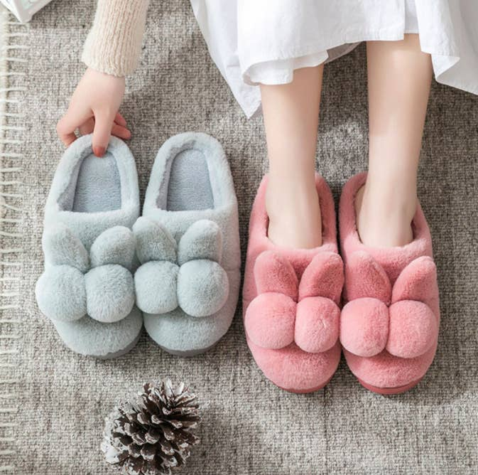 A person wearing the bunny-shaped slippers while sitting next to a pair in a different colour