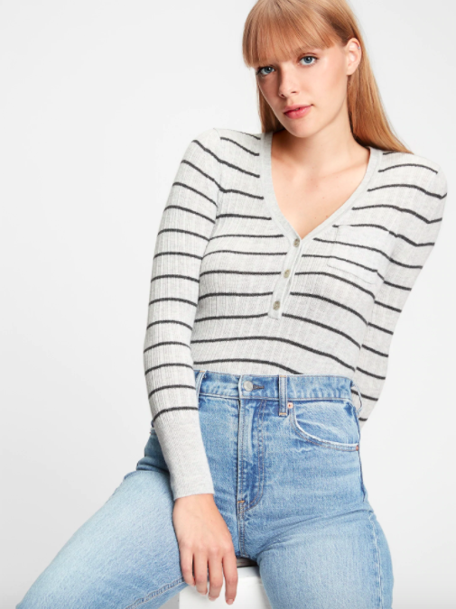 A person wearing the striped henley sweater tucked into a pair of light wash jeans