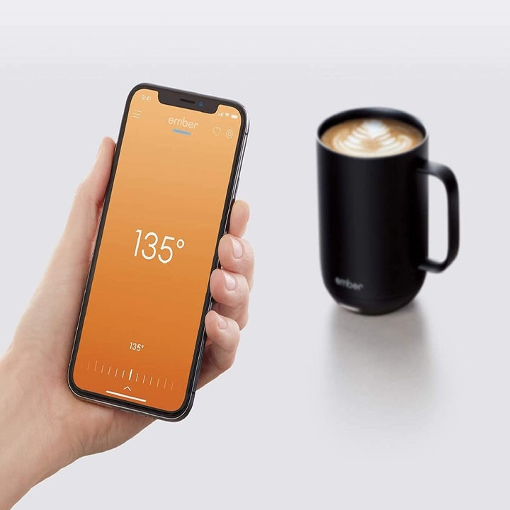 Model holding smartphone in front of Ember mug with the accompanying app