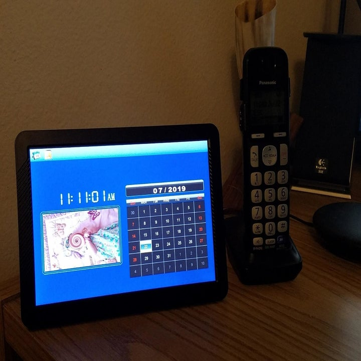 Reviewer photo of digital picture frame on table with calendar feature displayed