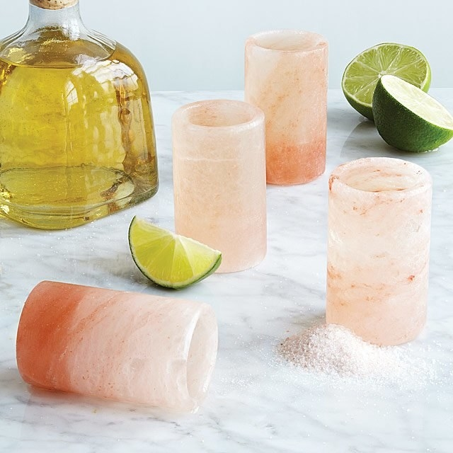 four pink shot glasses next to limes and tequila