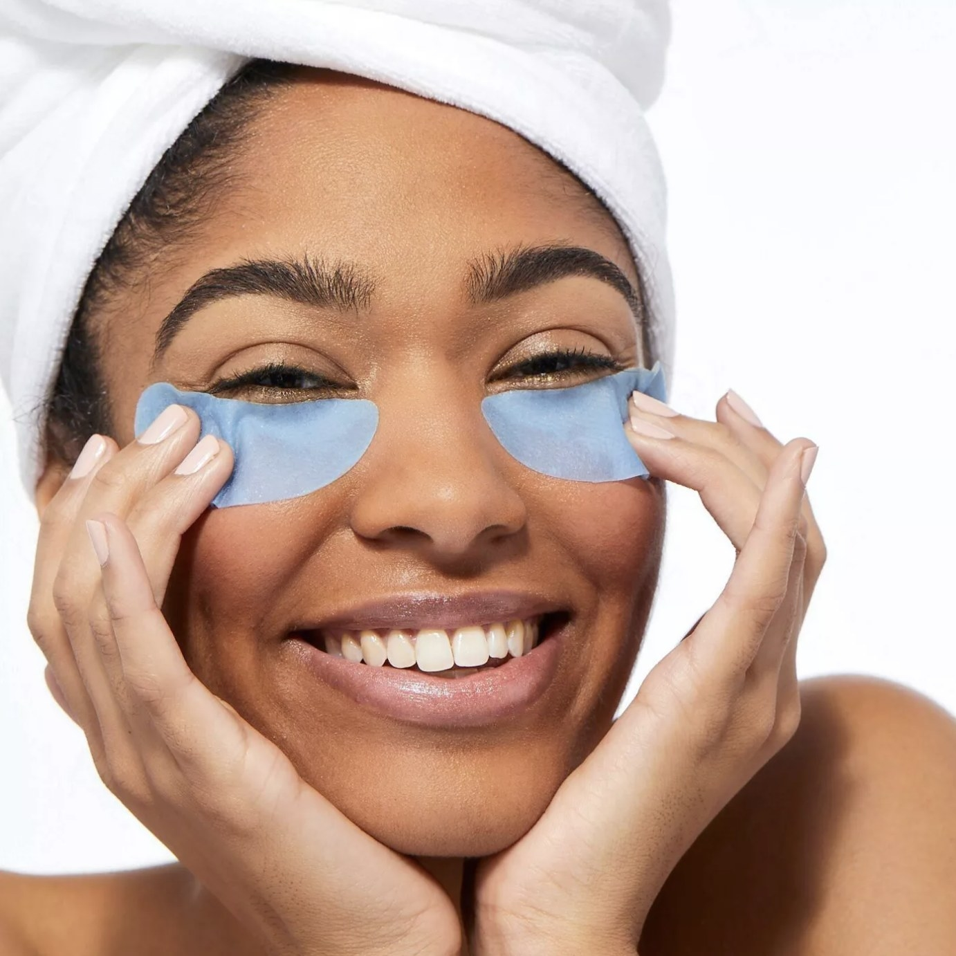 Model is wearing light blue under-eye patches on their face