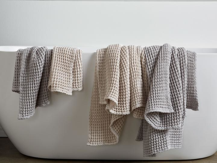 waffle towels draped over the side of a bathtub