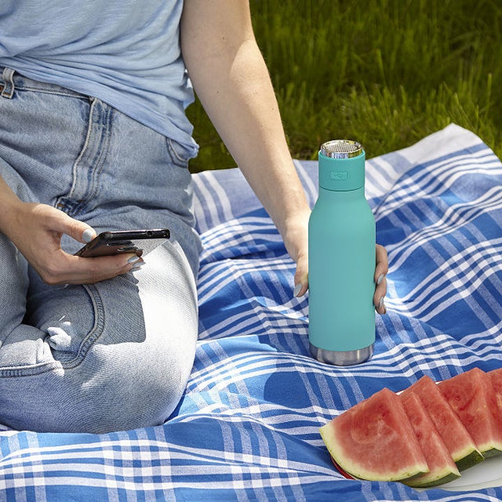 Model holding teal Bluetooth water bottle on picnic blanket