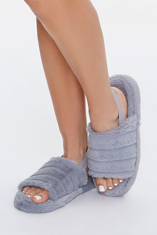 A model in plush gray blue open toed slippers with a strap on the back heel