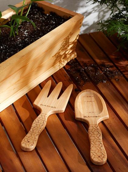 A pair of bamboo garden tools next to a bamboo planter box