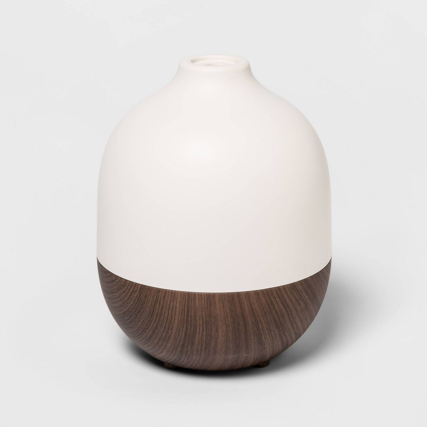 The diffuser, which has a woodgrain bottom, white top, and looks like a teardrop vase