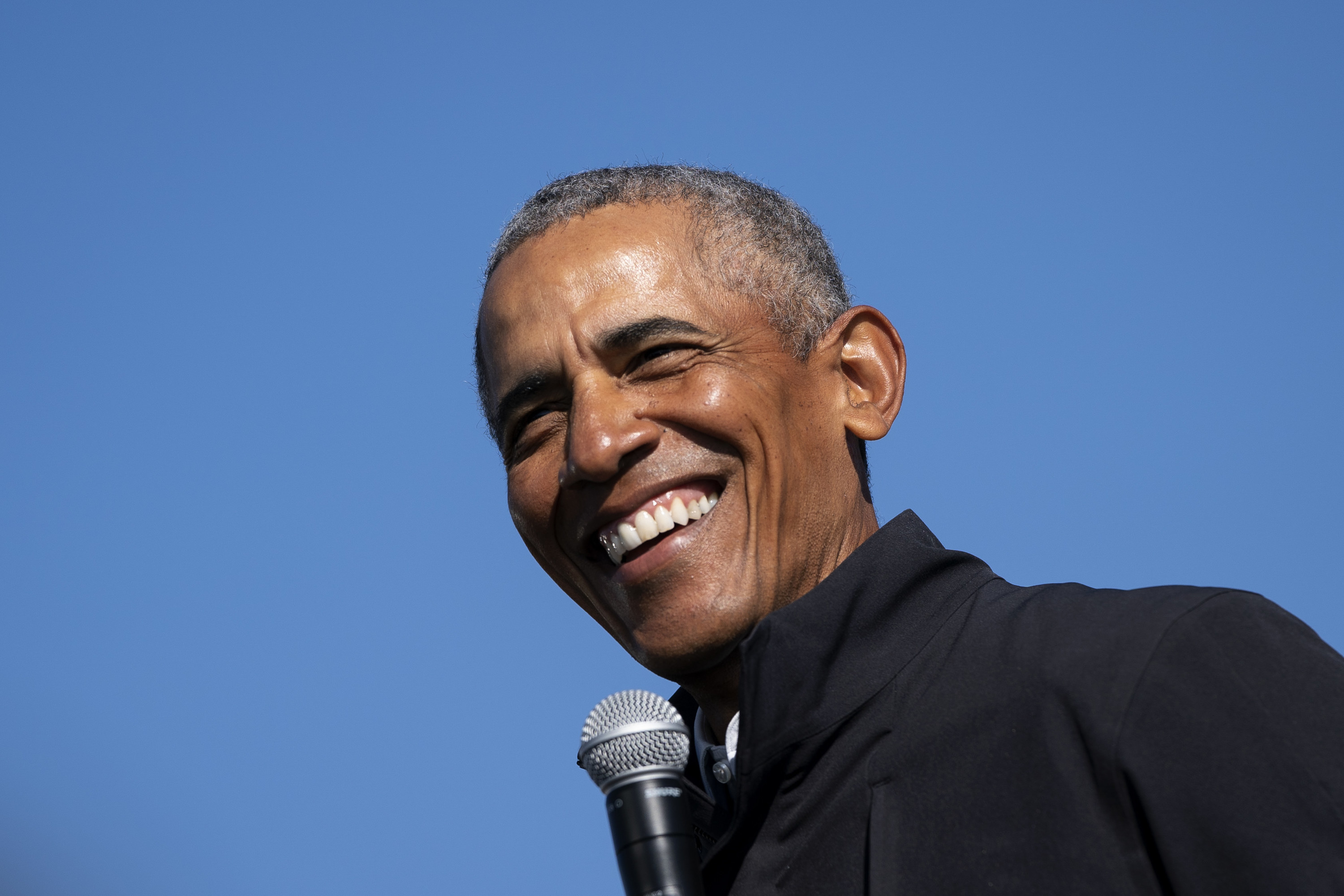 Former U.S. President Barack Obama smiling at a drive-in campaign rally