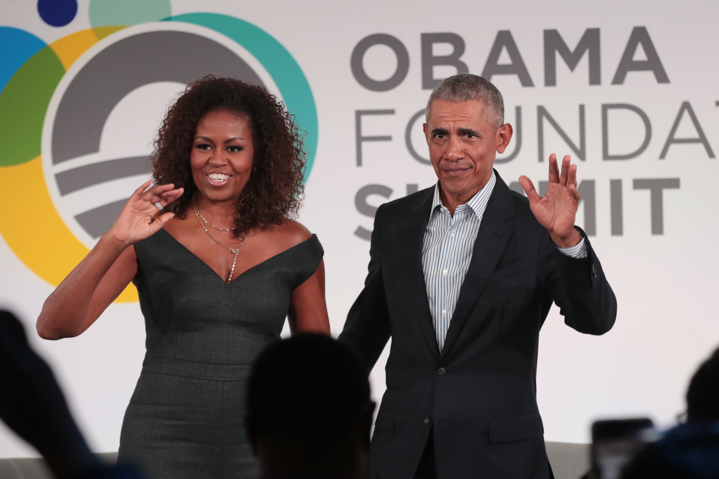 President Obama and former First Lady Michelle Obama waving to a crowd at the close of the Obama Foundation Summit in 2019