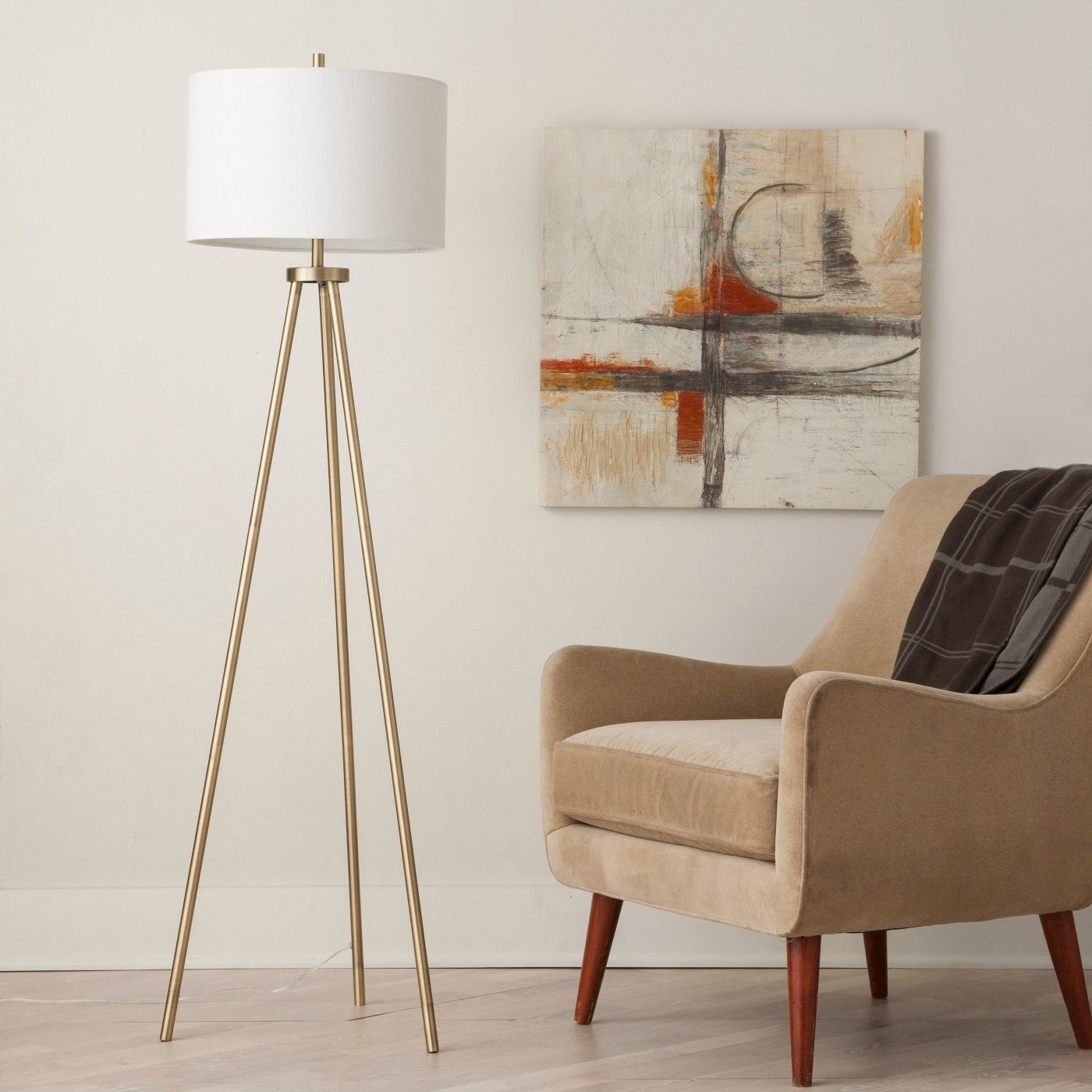 The lamp, which is taller than an arm chair, has three long, thin brass legs, and a white circular lampshade at the top