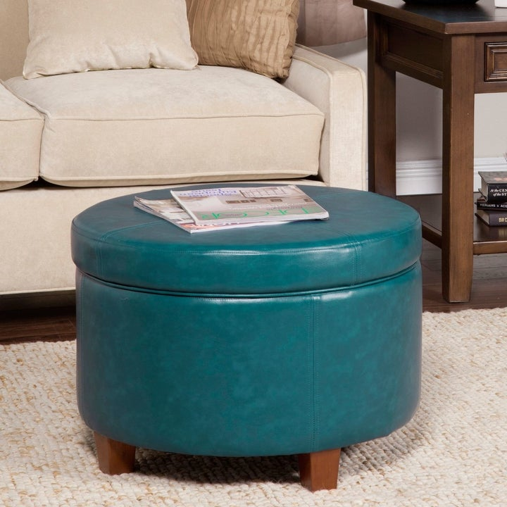 The ottoman, which is round and has very short wooden legs, in a closed position