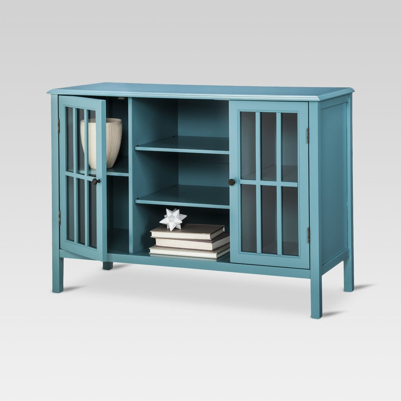 The cabinet in teal, which has four small legs, two cupboard areas on the side with glass-panelled doors, and three shelves in the middle section