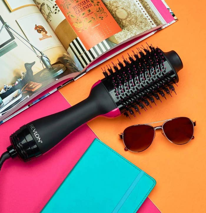 The Revlon hair dryer next to a vibrant magazine, e-reader, and sunglasses to show its size