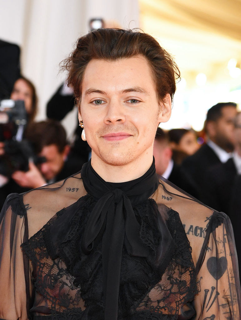 Harry at the 2019 Met Gala wearing a sheer blouse with ruffles and lace detailing and a single drop pearl earring