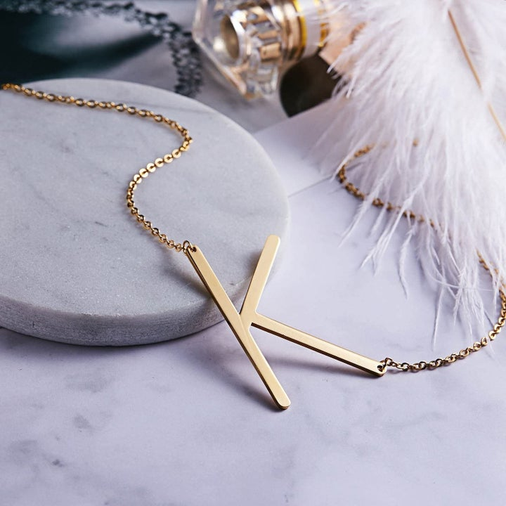 "the gold ""K"" necklace"