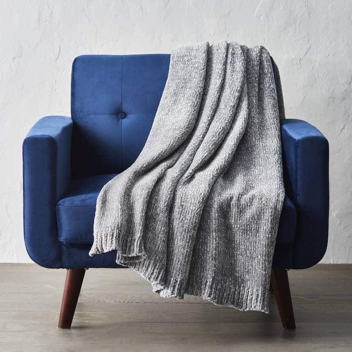 a chenille throw draped over a blue chair