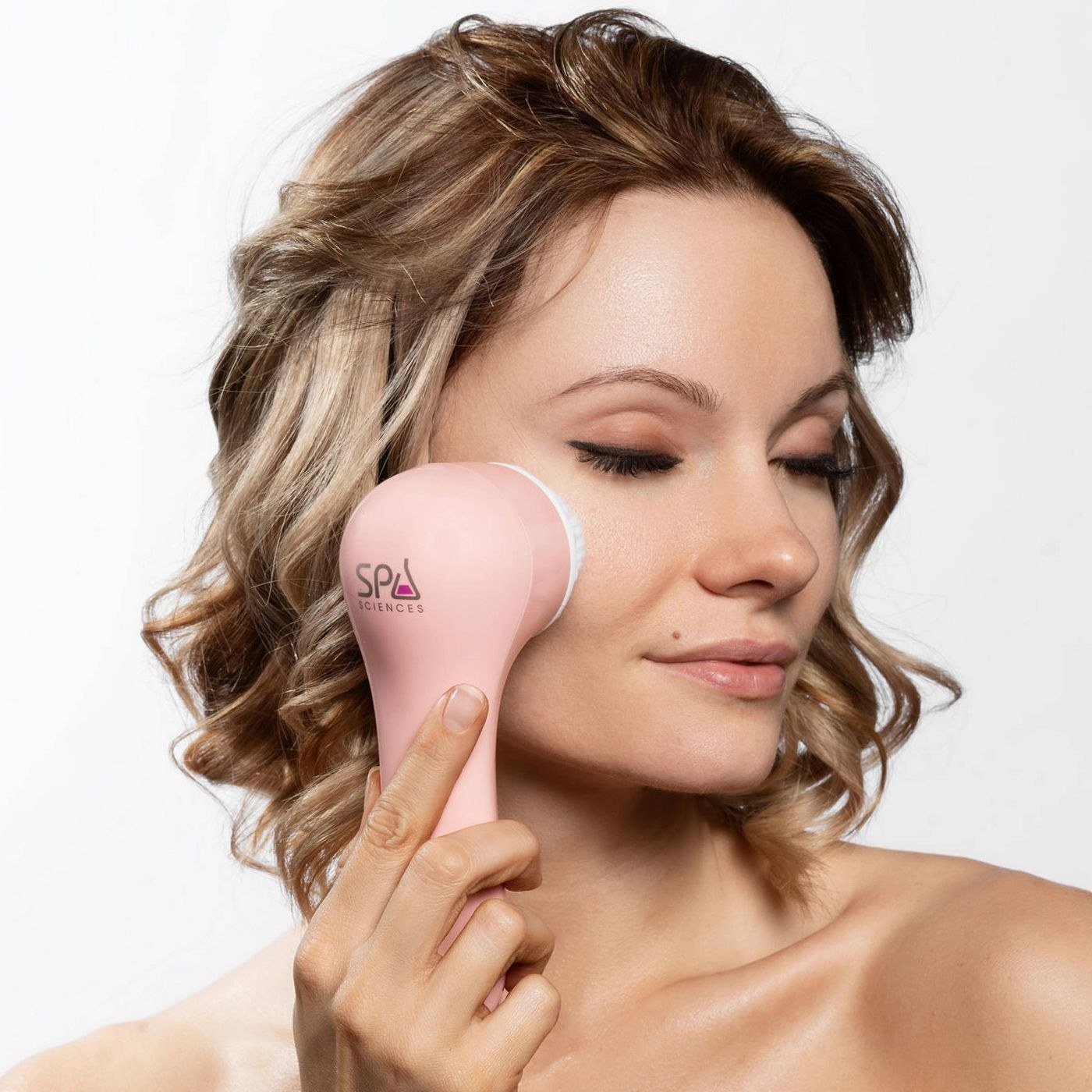 The cleansing brush in pink being used on a model's skin