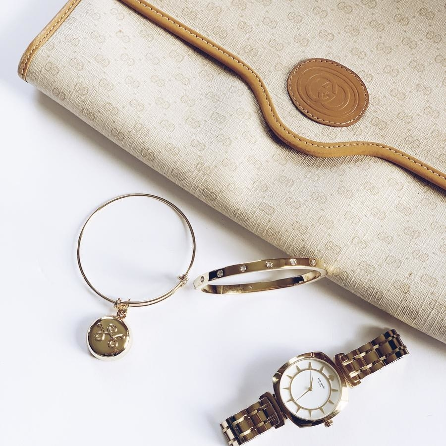 the gold bracelet styled on a table with a watch and purse