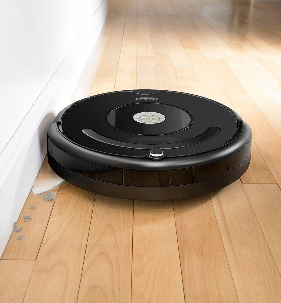 The Roomba sweeping up dust alongside a wall