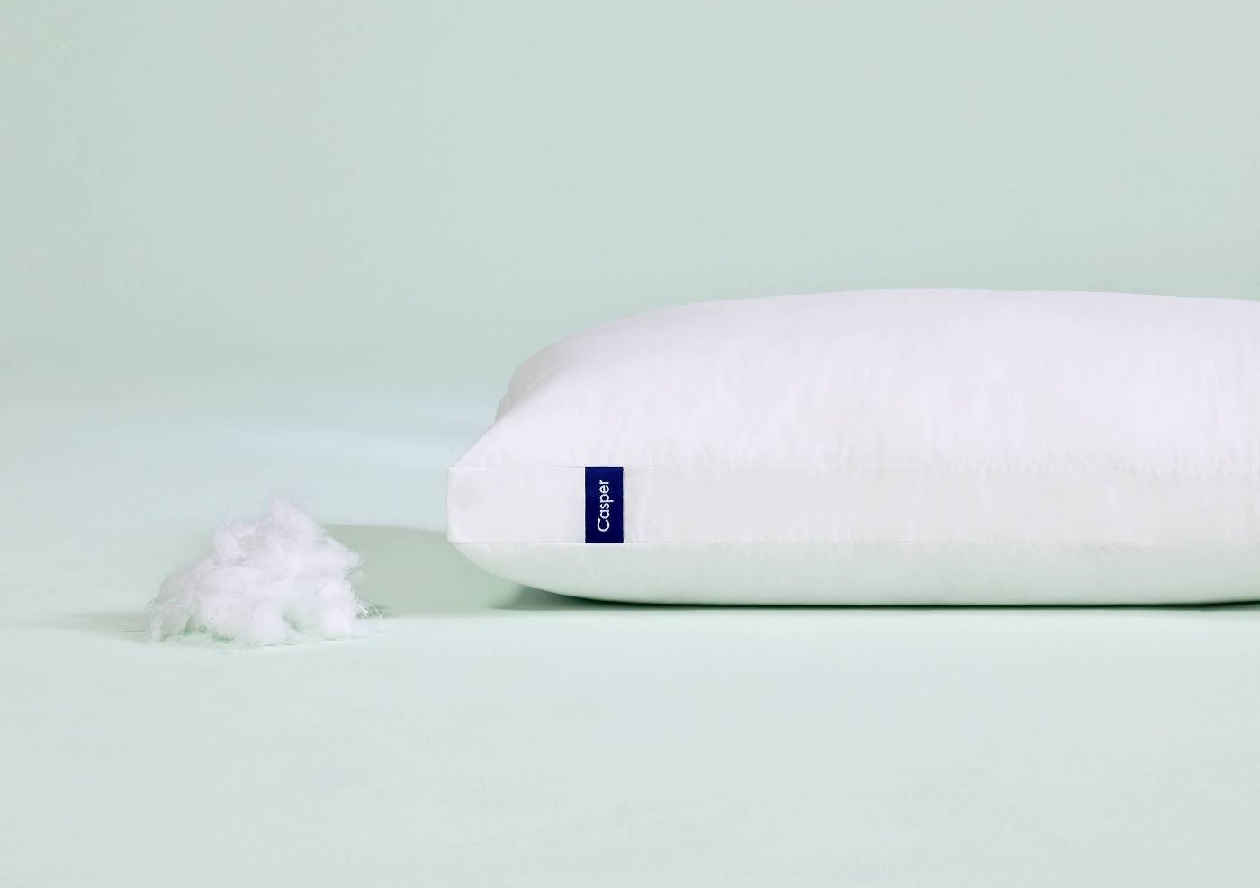 The Casper pillow next to a mound of stuffing to show its inside contents