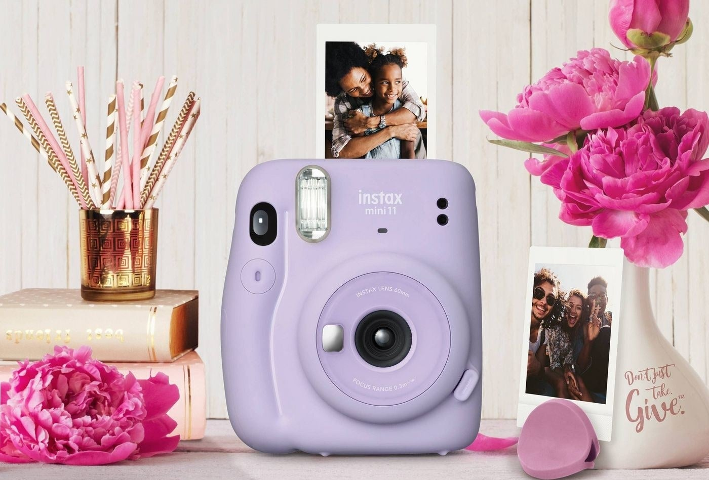 The Fuji Instax Mini in purple surrounded by pictures it has taken