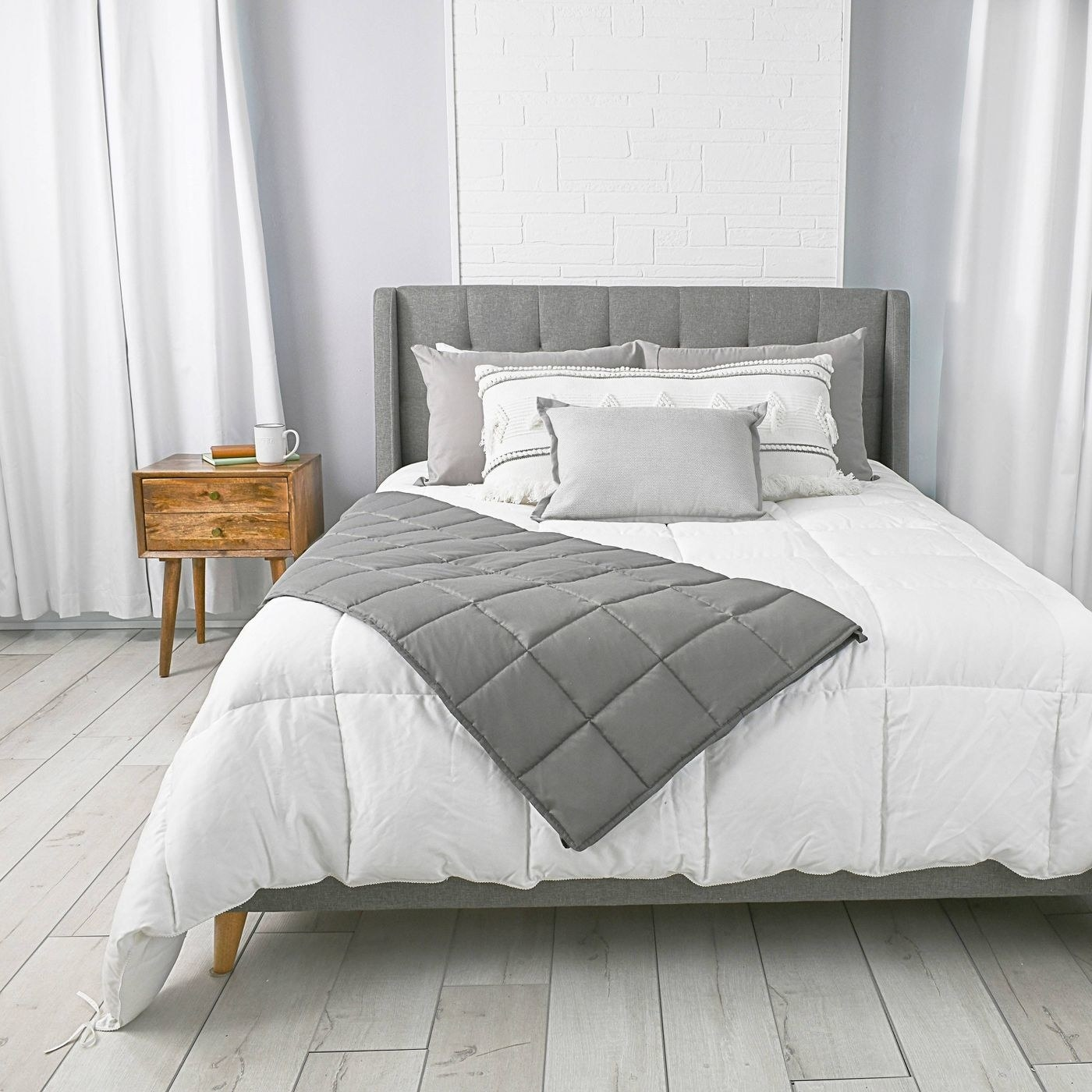 The weighted blanket in gray draped over a bed