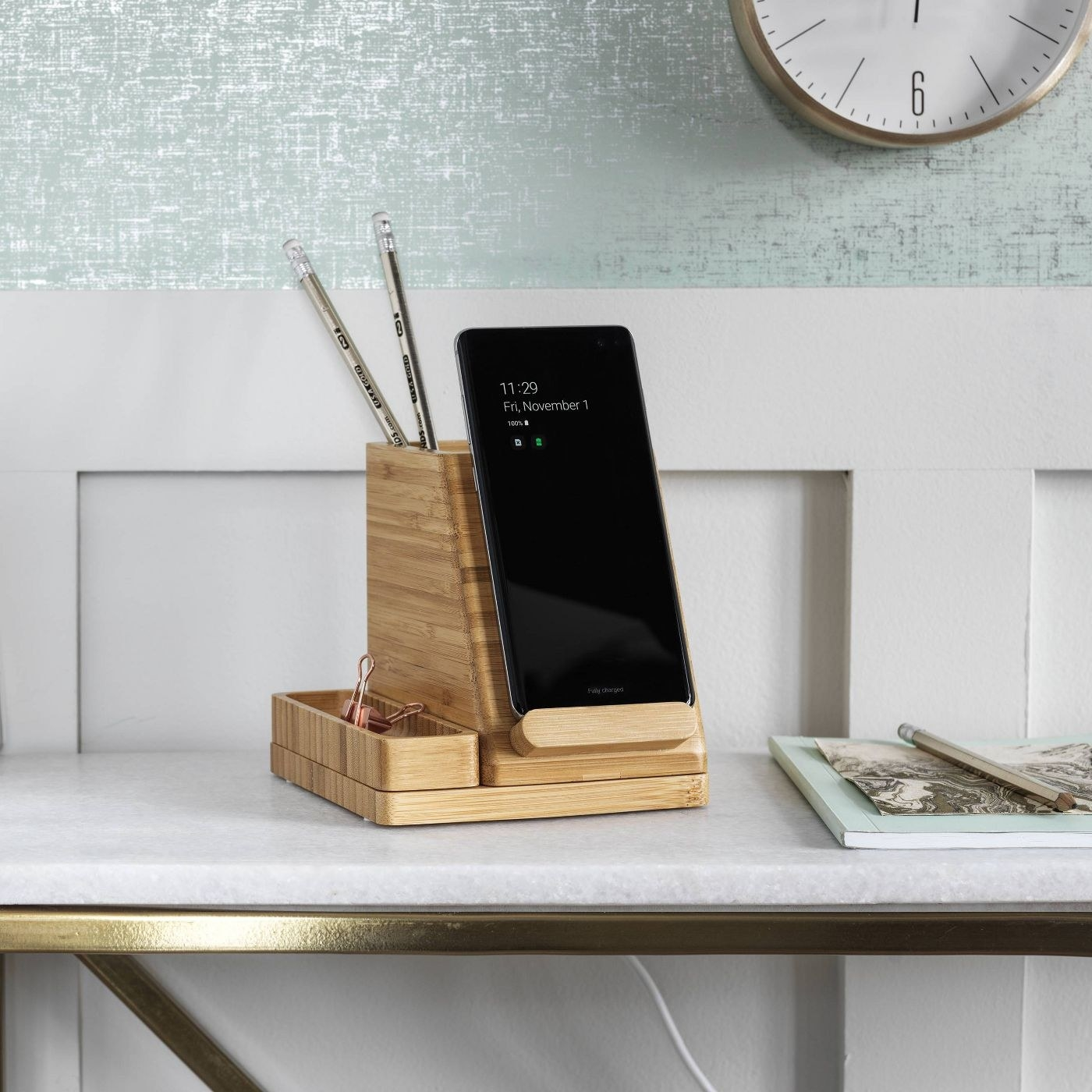 The desk storage unit holding a phone and several pencils